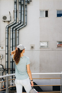 Girl stands near the wall of a commercial building, view from the back