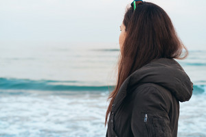Girl stands sideways to the camera and looking at the sea. Young woman in warm jacket looking at the sea while walking on the beach in spring.