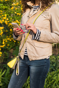 Girl uses the phone on the background of yellow flowers, she is dressed in a beige jacket, blue jeans and a striped shirt, at the shoulder yellow gray bag. In her hand with red manicure white phone.