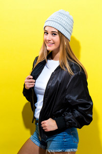 Girl wearing a black jacket on a yellow background