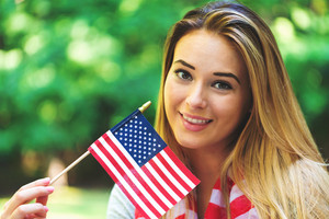 GIrl with an American flag on the fourth of July in her backyard