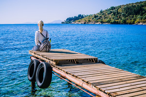 Girl with backpack on pier on the beach near Kalami looking into sea. Corfu Island, Greece