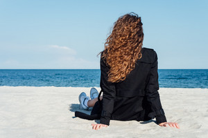 Girl with beautiful curly hair sitting on the beach in a coat and looking at the sea