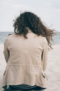 Girl with brown curly hair sits on the beach in windy weather, vertical cropping