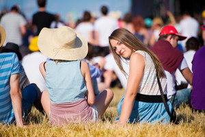 Girl with friends, group of teenagers at summer music festival, sitting on the grass, back view, rear, viewpoint