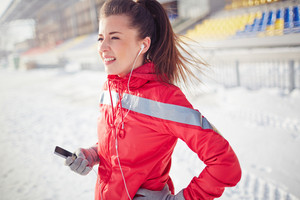 Girl with iphone in activewear spending leisure at stadium
