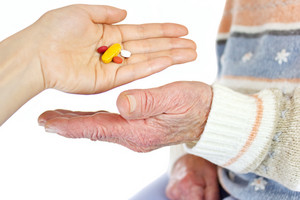 Giving pills to elderly woman over white background
