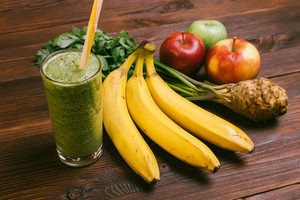 Glass of green smoothie with yellow straw on a wooden table next to bananas, apples and celery