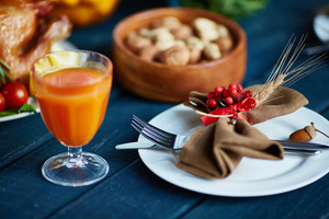 Glass of juice, plate with acorn, napkin, fork and knife on festive table