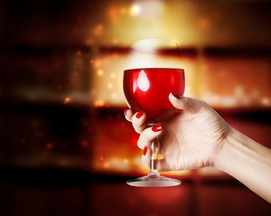 Glass of Red Wine in a young womans hand