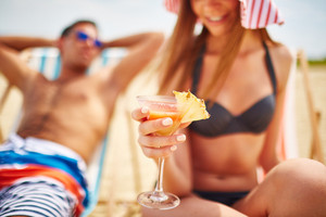 Glass of refreshing tropical cocktail held by young girl in bikini