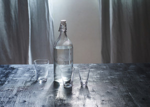 Glass of water with a bottle on wooden table