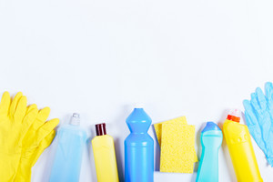 Gloves, sponges, bottles of cleaning fluids on a white table, space for text, top view