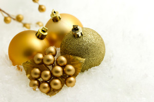 Gold christmas baubles and ornaments on white snow