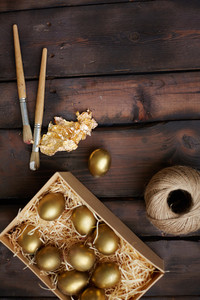 Golden Easter eggs in rectangular box with paintbrushes and thread on wooden background
