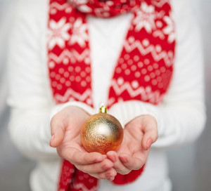 Golden toy ball on human palms