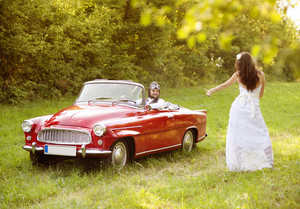 Gorgeous bride and groom having fun with red retro car in nature