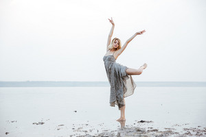 Graceful young woman in long dress dancing outdoors in lake