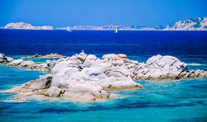 Granite rocks in sea, amazing azure water, white sailboats in background near Porto Pollo, Sardinia, Italy