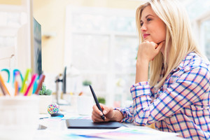 Graphic designer using her graphic tablet in an office