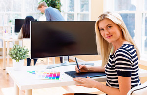 Graphic designer using her pen tablet in a bright office