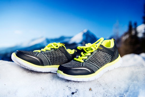 Gray running shoes laid outside on snow