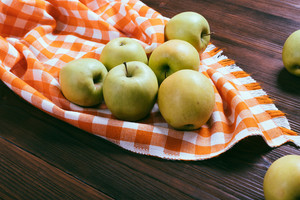 Green apples on a wooden table and orange checkered tablecloth