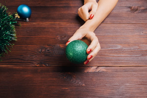 Green Christmas ball in a female hand with red nail polish