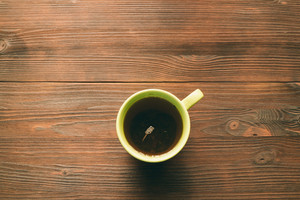 Green Cup of tea on wooden table, top view, copy space