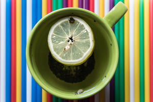Green cup of tea with lemon on a bright colored striped background