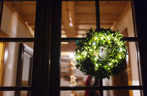 Green mistletoe wreath hang on glass door
