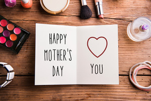Greeting card with Happy mothers day sign and various beauty products laid on table. Studio shot on wooden background. Flat lay.