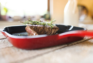 Grilled beef steak on a pan with fresh rosemary spring