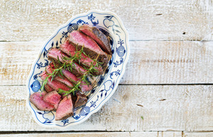 Grilled beef steak, sliced on a serving plate with fresh rosemary spring