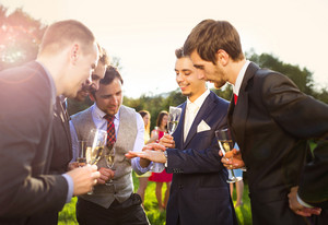 Groom with four happy groomsmen toasting at the wedding reception outside