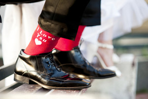 Groom's funny feet with love sign on red socks.