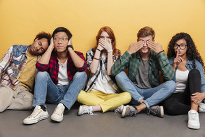 Group of amusing playful young people covered eyes, ears and mouth over yellow background