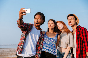 Group of amusing young friends taking selfie with cell phone and making funny faces outdoors