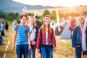 Group of beautiful teenagers with backpacks arriving at summer music festival