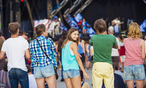 Group of beautiful teens at concert at summer festival