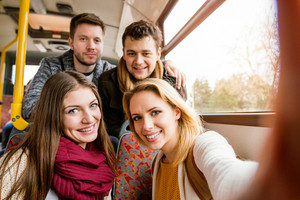 Group of beautiful young people traveling by bus, taking selfie