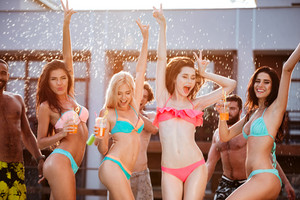 Group of best friends having fun dancing at swimming pool outdoors
