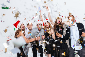 Group of cheerful excited friends in santa claus hats celebrating new year over white background