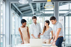 Group of cheerful successful business people with laptop standing and talking together in office