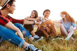 Group of cheerful young friends talking and celebrating with beer and soda outdoors