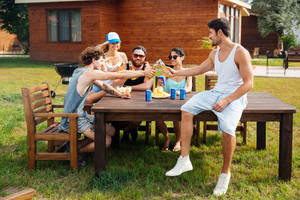 Group of cheerful young people celebrating and drinking beer at the table outdoors