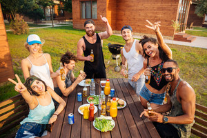 Group of cheerful young people having fun and eating at the table outdoors