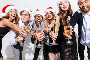 Group of cheerful young people in santa claus hats with champagne celebrating new year over white background