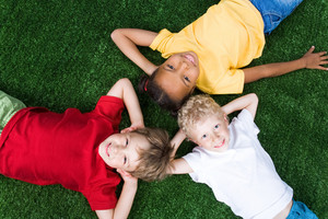 Group of children lying on the grass together