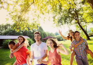 Group of five teenage friends having fun in park